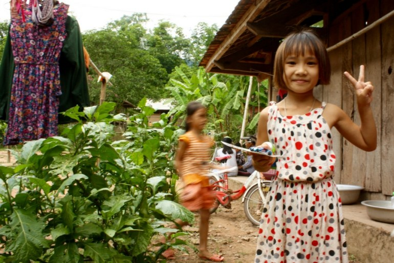 Image of a smiling young girl giving the peace sign in Xom Pung Village Vietnam.