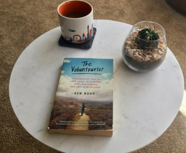 Image of book 'The Voluntourist' on a table with coffee and cactus.