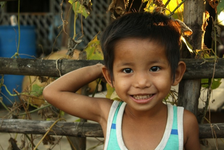 A young boy leaning against a fence smiling as we distribute bags of rice around his village.