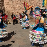 Image of men dressed in colorful costumes dancing for the Corpus of San Cristobal festival in Cusco Peru.
