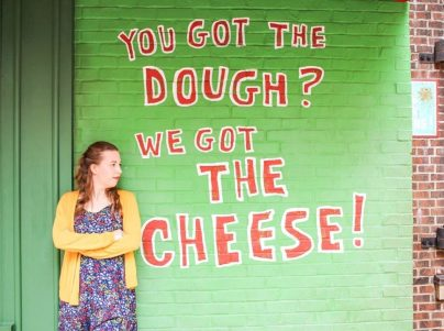 "A green wall with red letters outlined in white that reads ""You got the dough? We got the cheese!"" in Disney's Hollywood Studios."