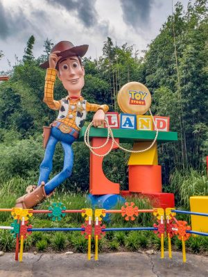 A statue of Woody from Toy Story stands next to the sign for Toy Story Land in Hollywood Studios.