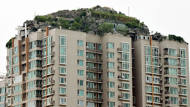 An Illegal Mountain Constructed Atop a 26 Story Residential Building in Beijing mountains China architecture