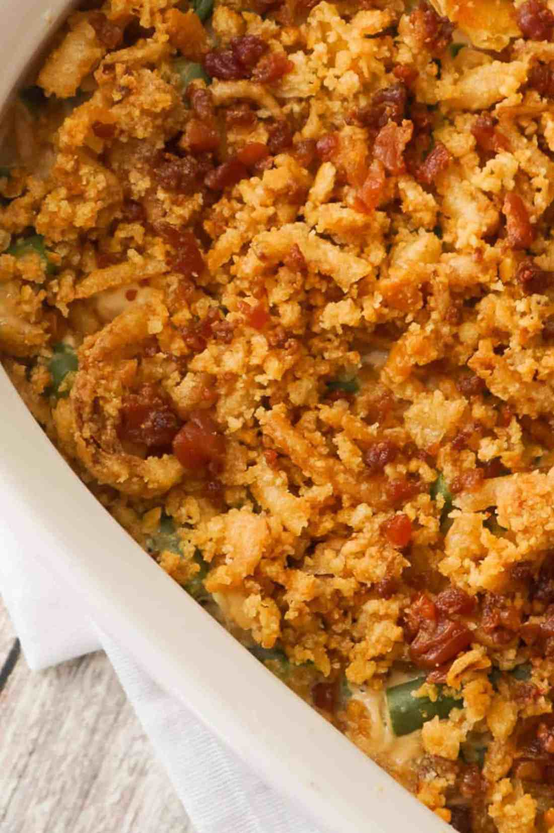 Cream Cheese and Bacon Green Bean Casserole is a holiday side dish recipe made with Lipton onion soup mix and topped with Ritz cracker crumbs, French's fried onions and crumbled bacon.