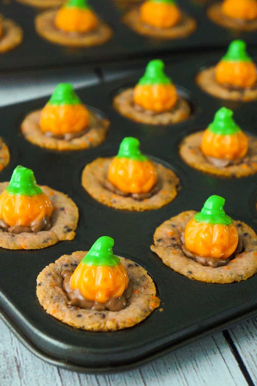 Halloween Sugar Cookie Cups are an easy dessert recipe your kids will love. These cute Halloween cookies are filled with milk chocolate and topped with pumpkin gummy candies.