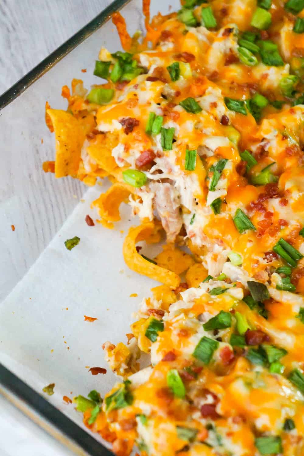 Chicken Bacon Ranch Frito Pie is a quick and easy dinner recipe using rotisserie chicken. This tasty casserole starts out with a base of Frito's corn chips topped with a mixture of shredded chicken, real bacon bits, green onions and ranch dressing, finished off with a layer of shredded cheese.