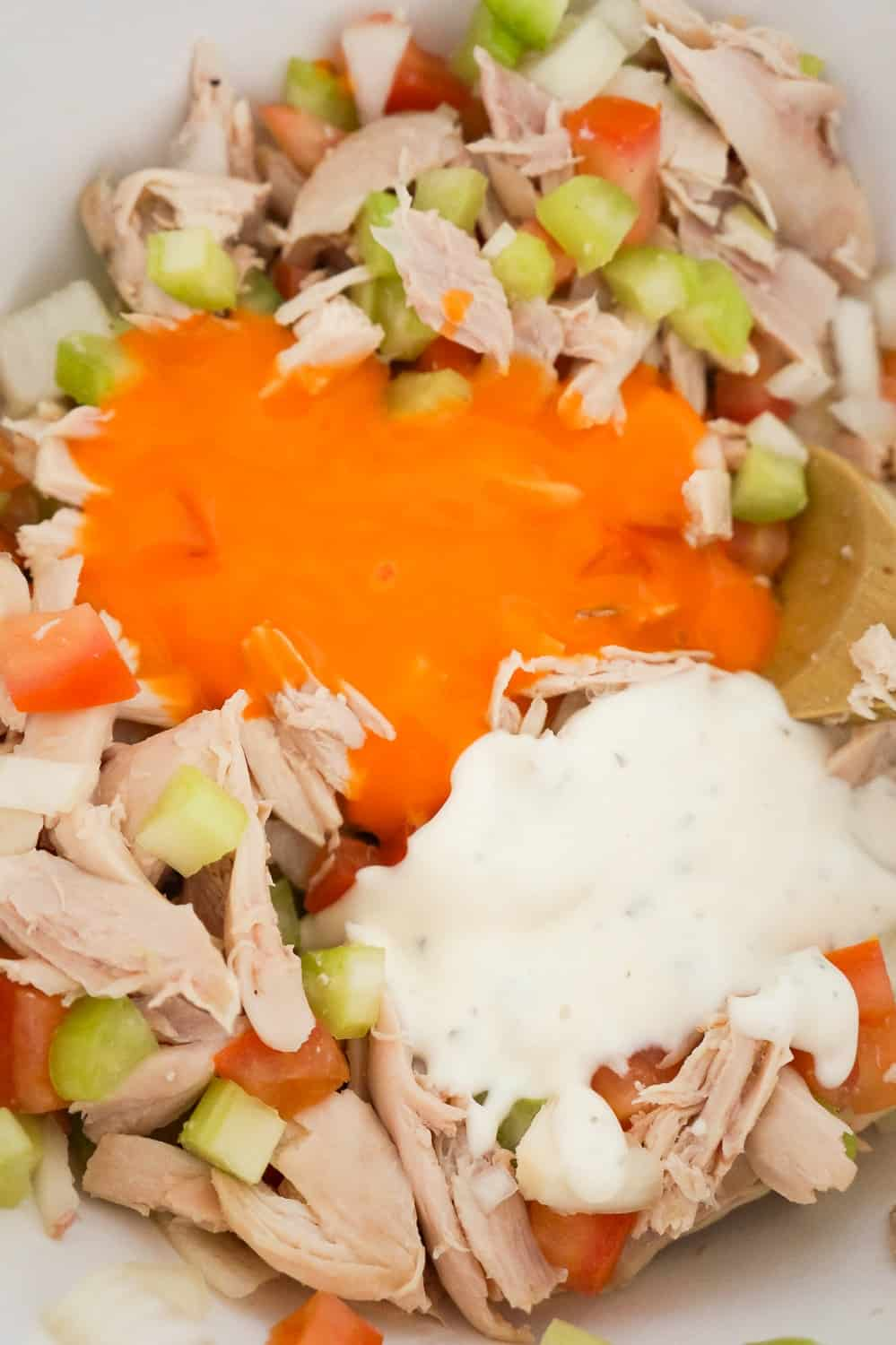 buffalo sauce and ranch dressing on top of shredded chicken and diced vegetables in a mixing bowl
