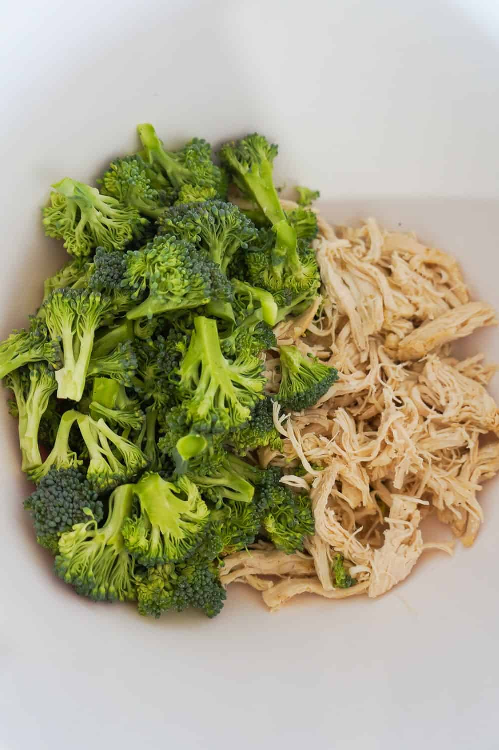 broccoli florets and shredded chicken in a mixing bowl