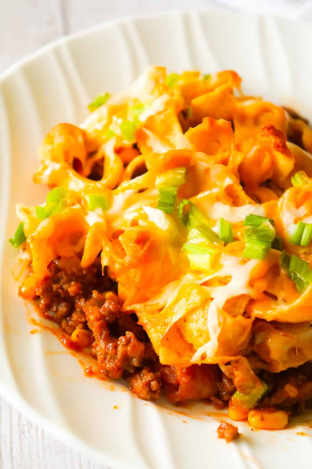 Frito Pie is an easy ground beef dinner recipe the whole family will love. This ground beef casserole starts with a chili base and is topped with Frito's corn chips, shredded cheese and green onions.