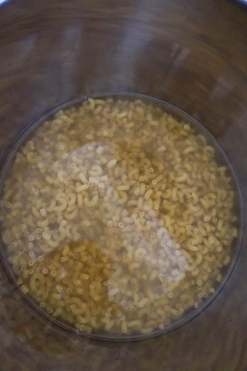 uncooked macaroni submerged in liquid in an Instant Pot