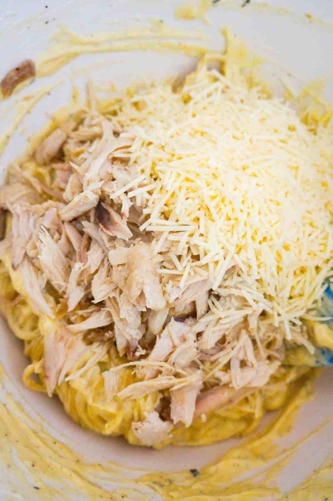 shredded Parmesan cheese and shredded turkey on top of creamy spaghetti in a mixing bowl