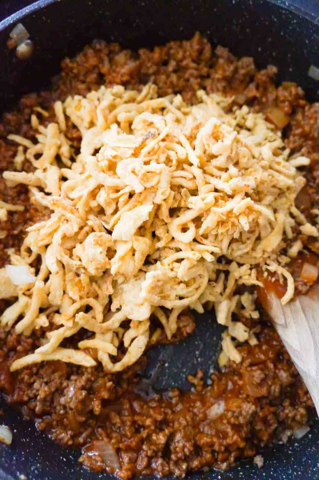 French's fried onions on top of sloppy joe mixture in a saute pan