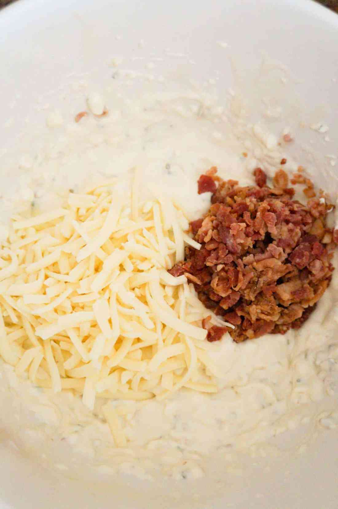 shredded mozzarella and crumbled bacon on top of cream cheese mixture in a mixing bowl