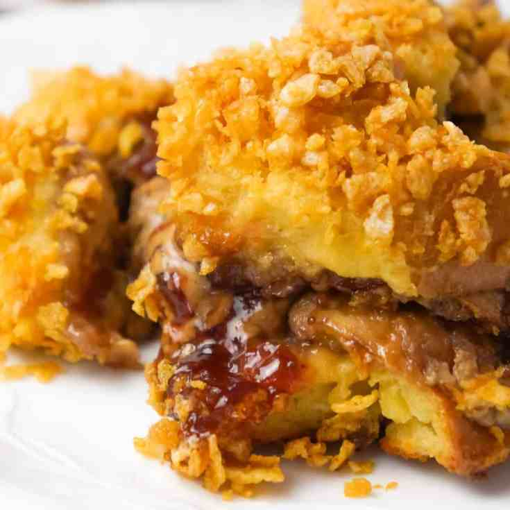 Peanut Butter and Jelly French Toast Casserole is a delicious breakfast casserole made with Italian bread loaded with peanut butter and strawberry jam and coated with Frosted Flakes.