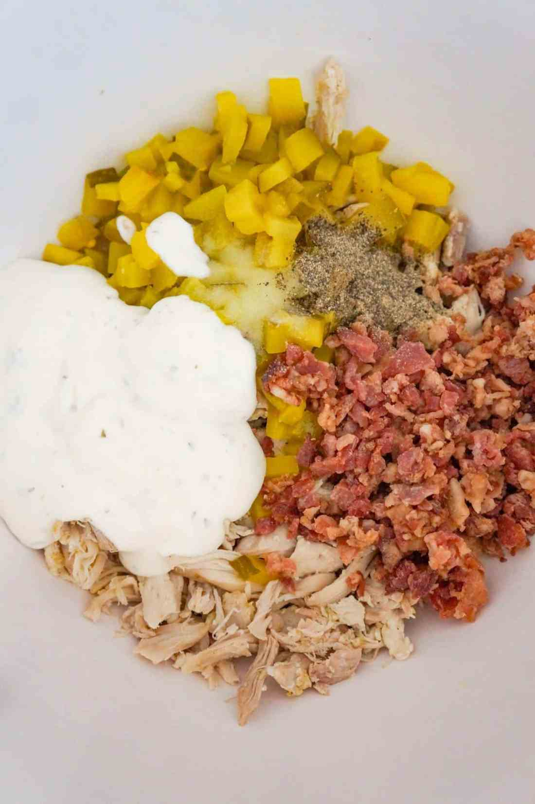 ranch dressing, shredded chicken, diced dill pickles and crumbled bacon in a mixing bowl