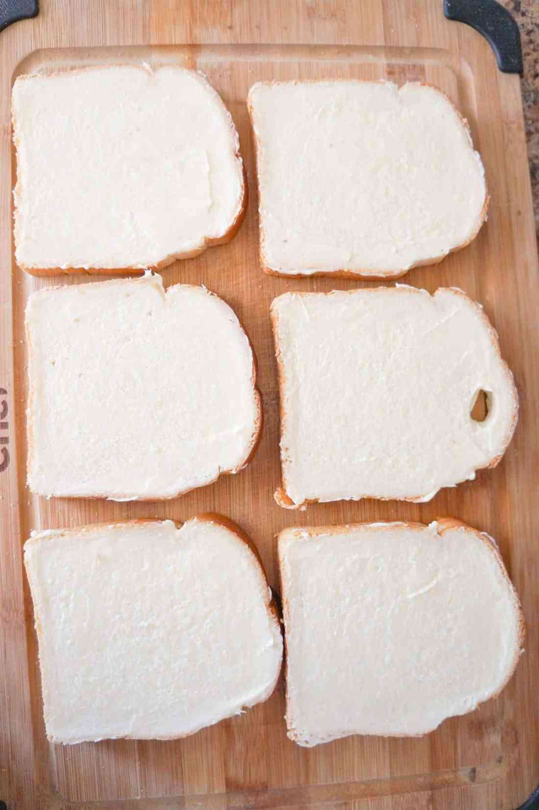 bread slices spread with margarine on a cutting board