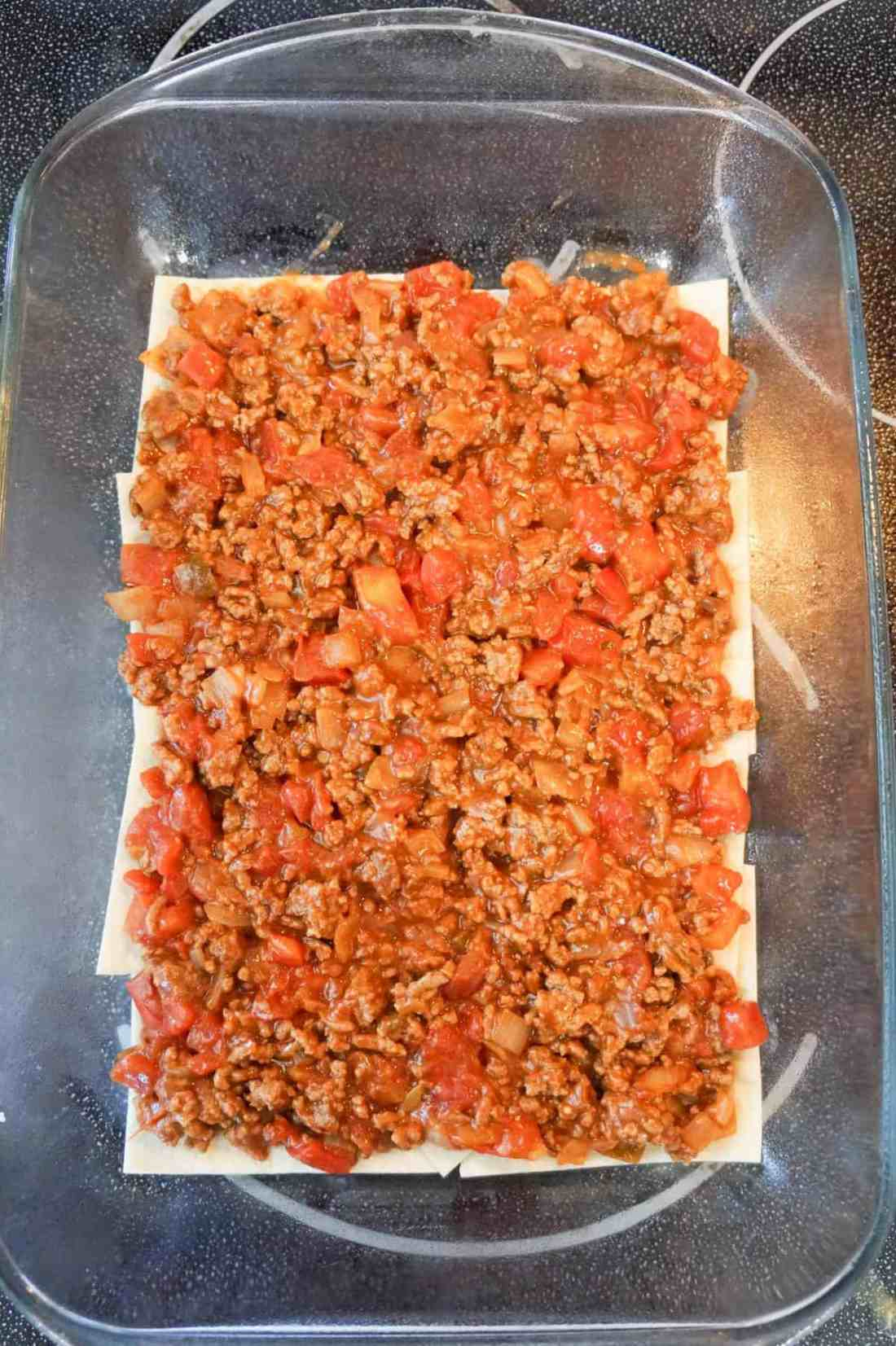 ground beef, salsa and Rotel mixture on top of flour tortilla pieces in a baking dish