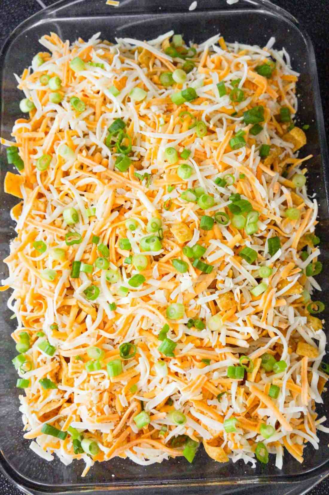 chopped green onions and shredded cheese on top of buffalo frito pie