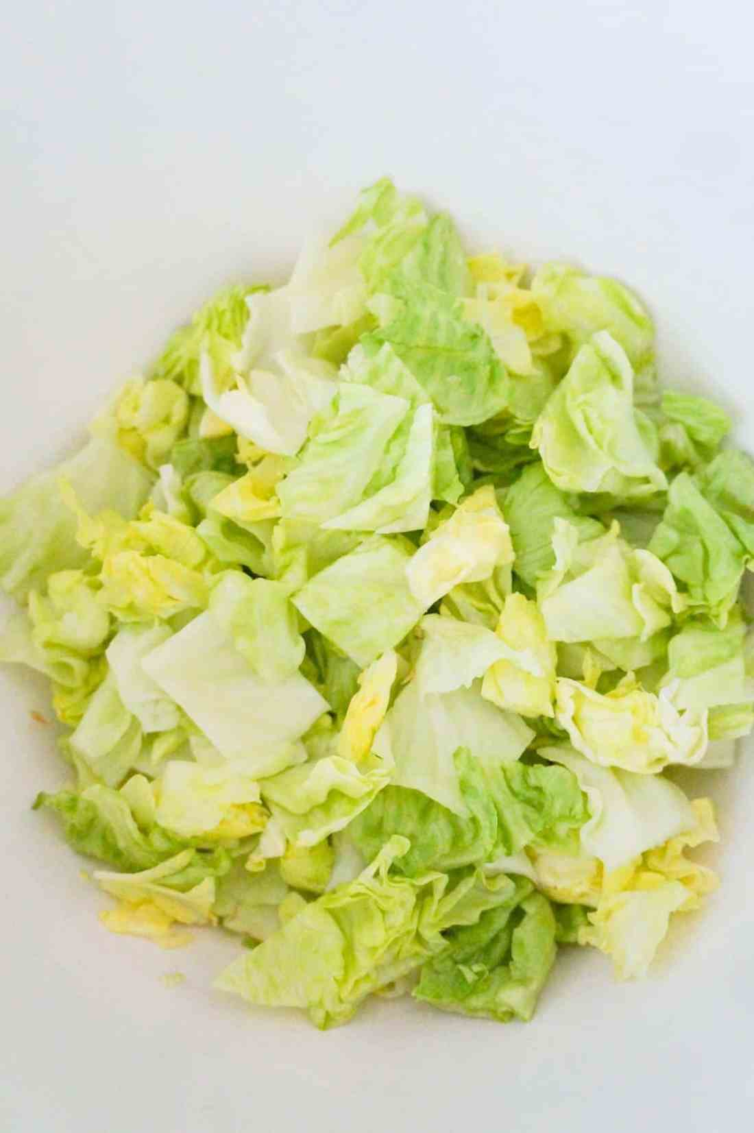 chopped iceberg lettuce in a mixing bowl