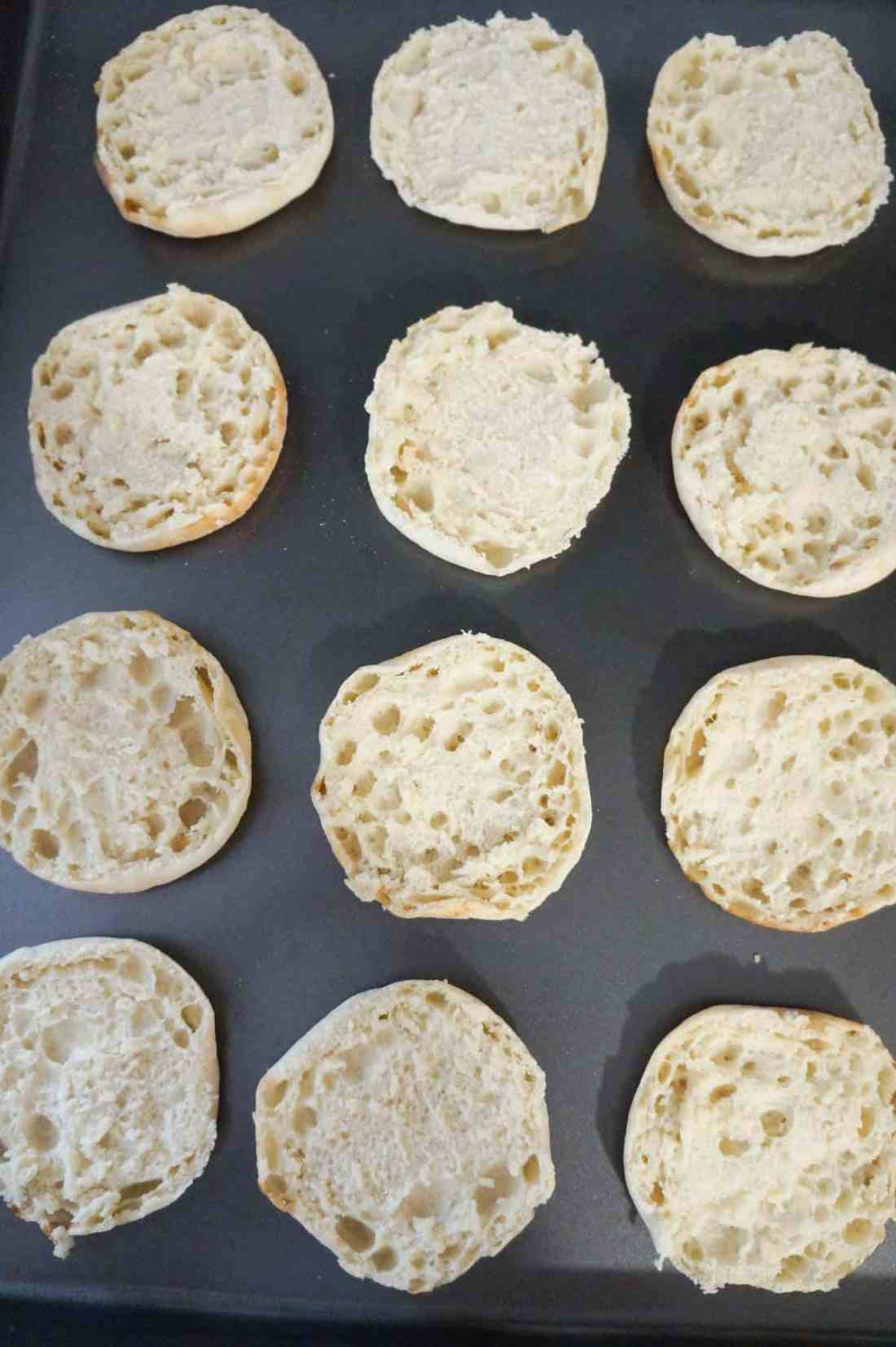 English muffin halves on a baking sheet