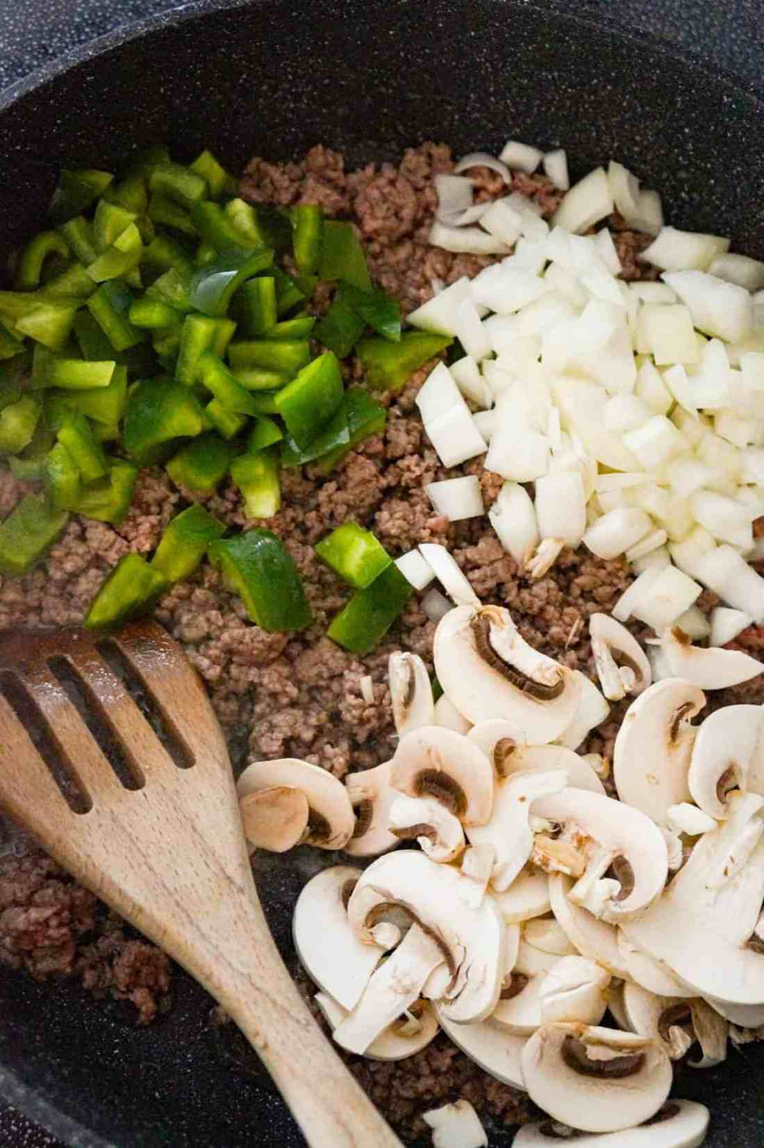 diced green pepper, diced yellow onion and sliced mushrooms on top of ground beef in a saute pan