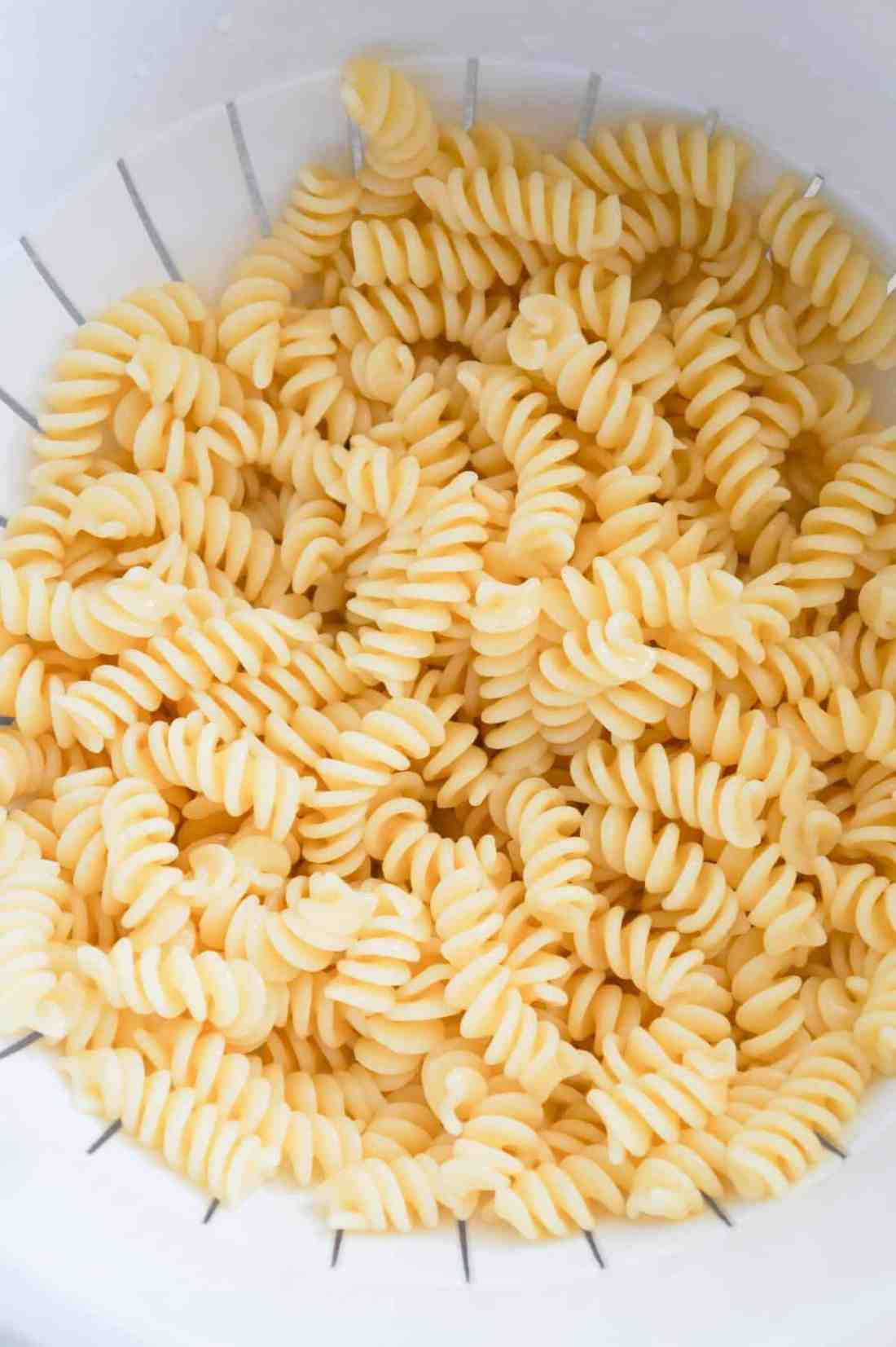 cooked fusilli noodles in a strainer