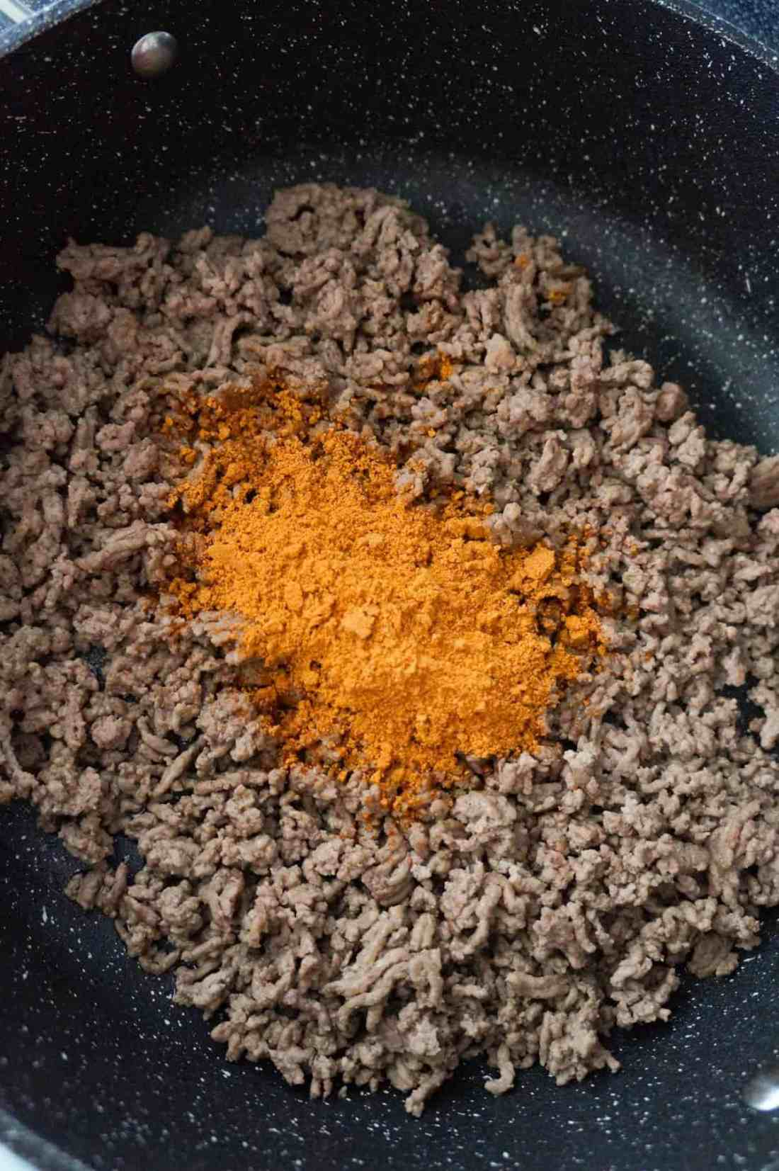 chili seasoning on top of cooked ground beef in a saute pan