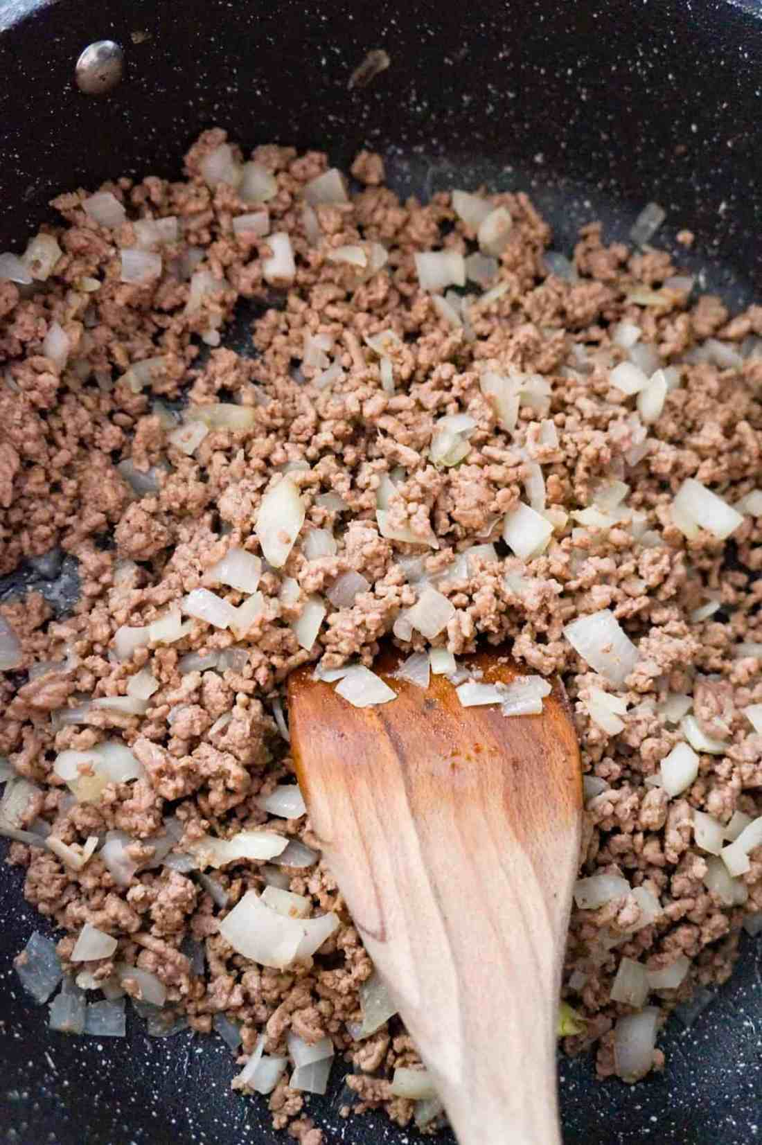 cooked ground beef and diced onions in a saute pan