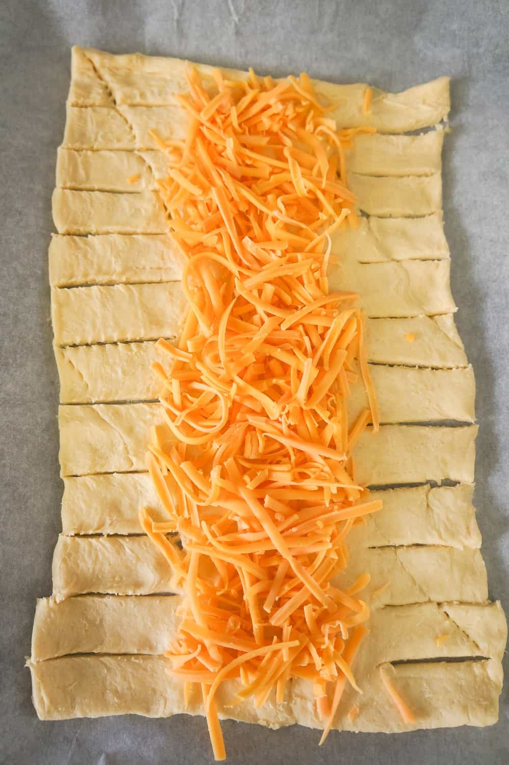 crescent dough topped with shredded cheddar cheese