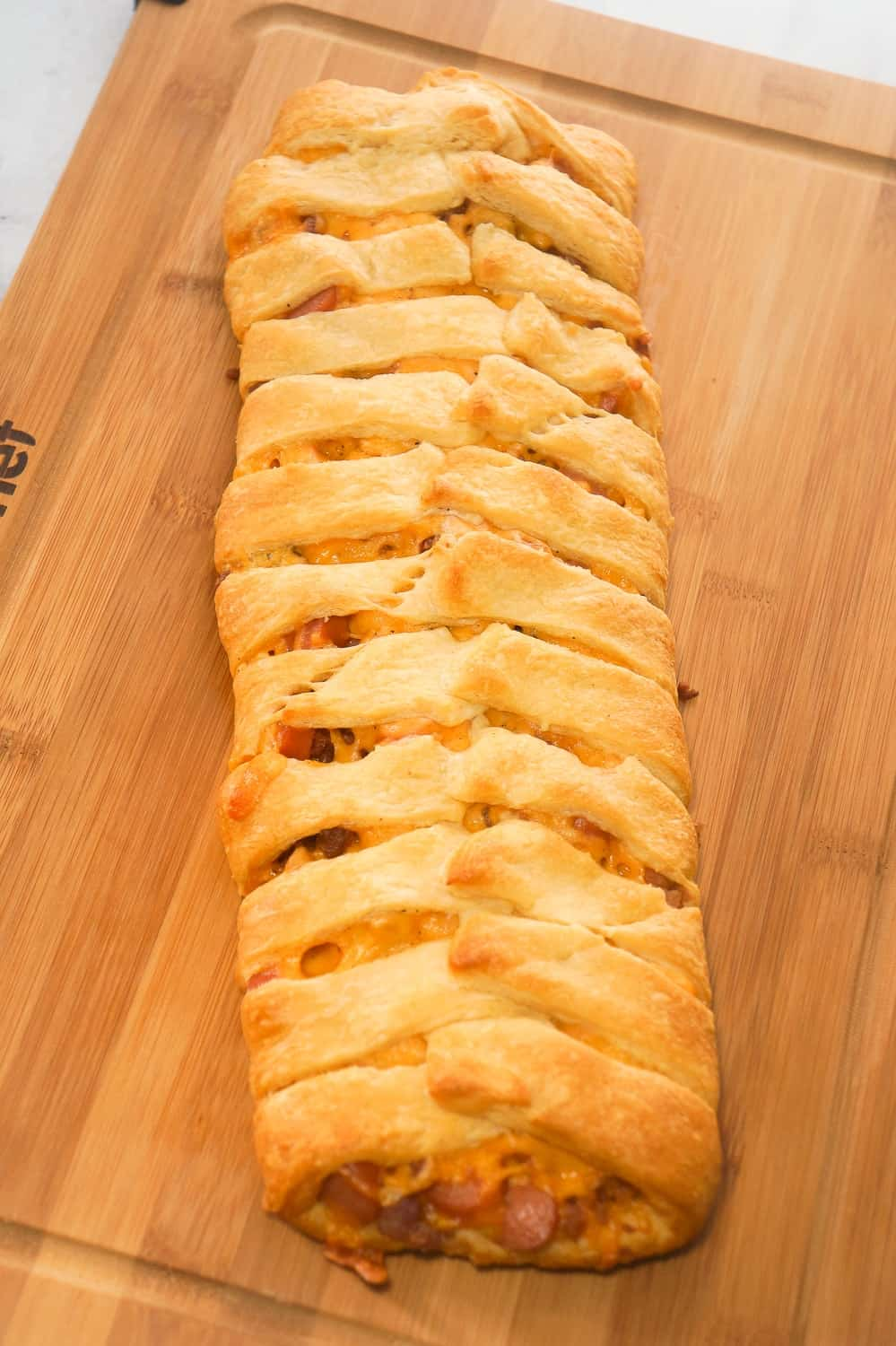 Bacon Cheese Dog Crescent Braid is an easy weeknight dinner recipe. This crescent bake is stuffed with wieners, bacon and cheese then topped with chili to make it a hearty comfort food dish.