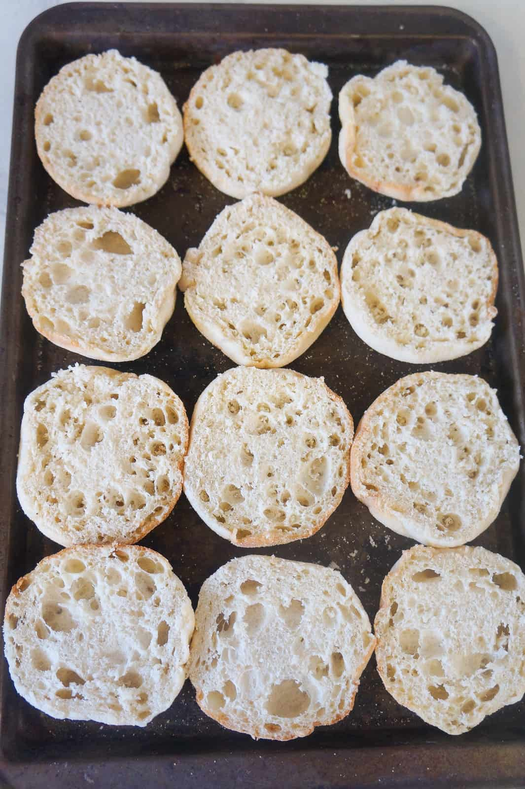 sliced English muffins on baking sheet