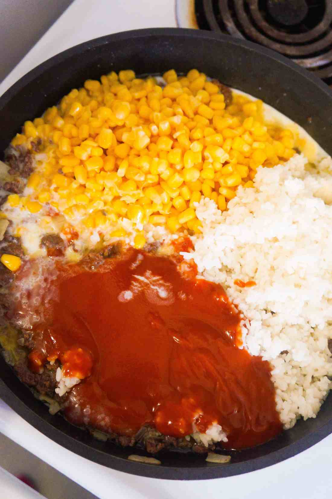 Cheesy Tomato Ground Beef and Rice ingredients in frying pan.