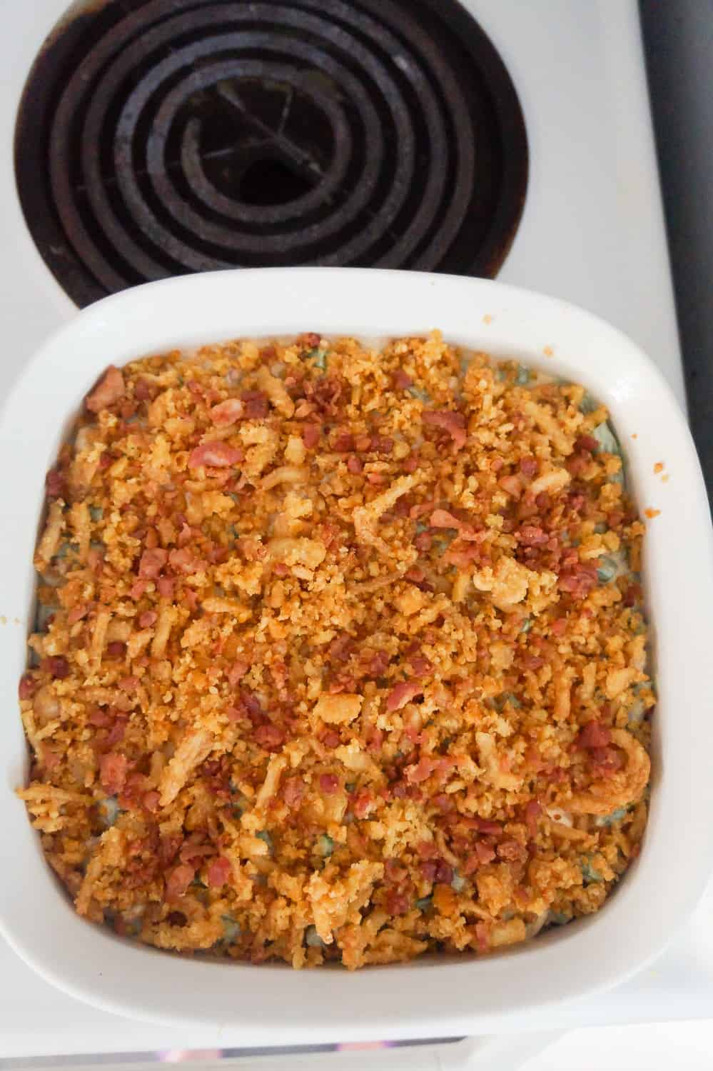Ritz cracker and fried onions on top of green bean casserole in baking dish