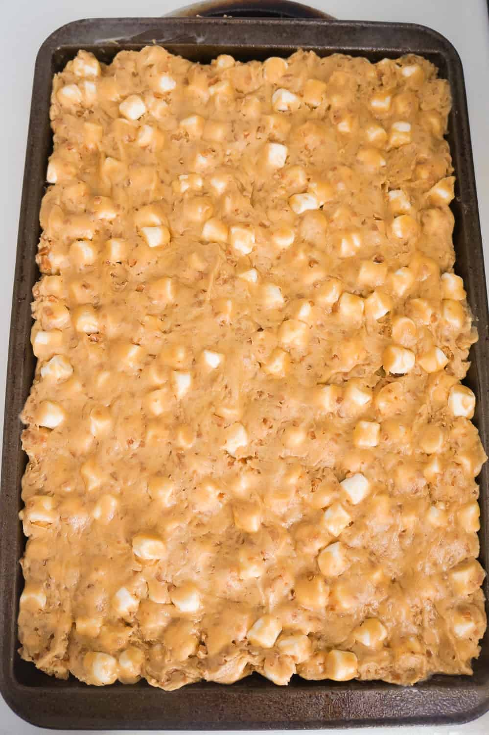 peanut butter marshmallow cookie dough spread out on baking sheet