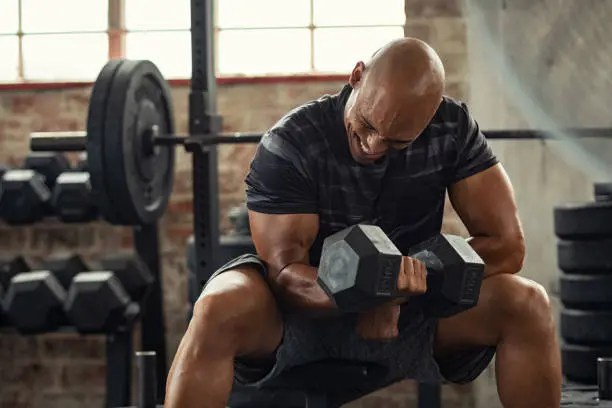 Man wincing while doing bicep curls