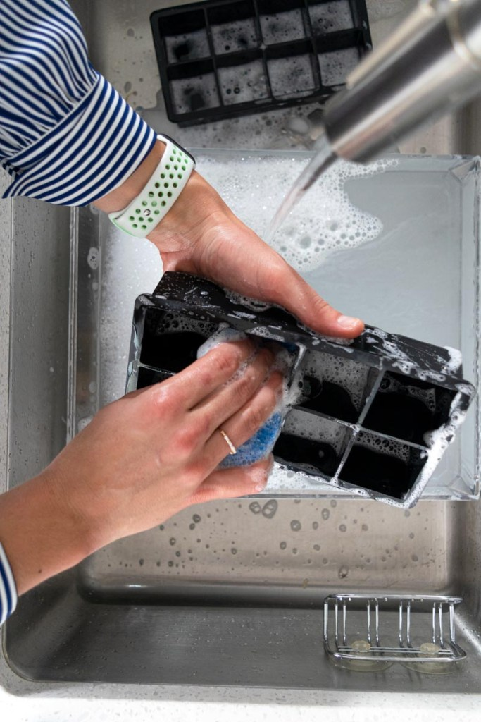 Hands washing ice cube molds in the sink
