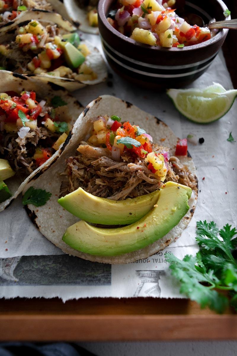Carnitas tacos with pineapple salsa and avocado slices