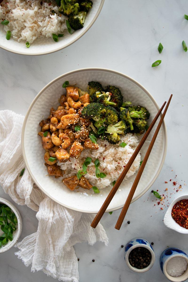 Cashew chicken in a bowl with chopsticks