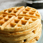 A tall stack of waffles with a waffle maker out of focus in the background