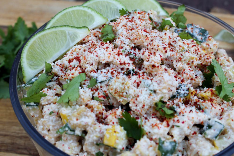Keto Mexican street corn salad in a white bowl topped with fresh chopped cilantro and lime wedges.