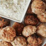 a plate full of Greek meatballs with a square dish of tzatziki in the corner