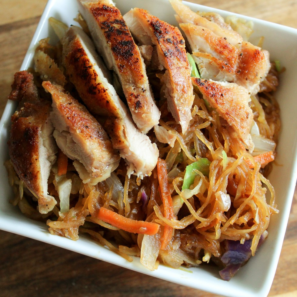 overhead photo of a white, square bowl, full of spaghetti squash chow mein topped with chicken