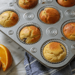 A muffin tin full of baked muffins with orange slices off to the side.