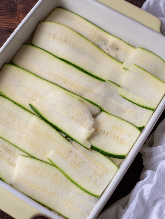 Zucchini slices layered in a casserole dish for a Low Carb Chicken Pesto Lasagna with Zucchini Noodles