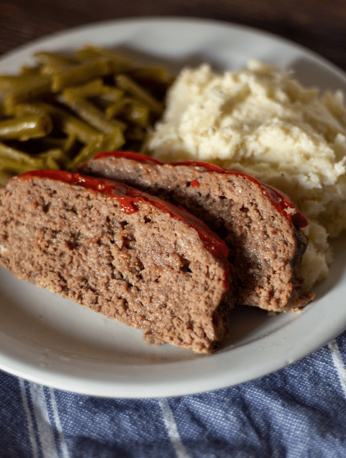 two slices of keto southern style meatloaf on a white plate with a side of green beans and mashed cauliflower.