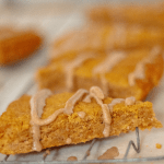 Keto pumpkin scones in a row on a baking rack, being drizzled with a glaze