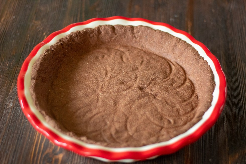 Empty chocolate pie crust in preparation for making a keto candy cane pie.