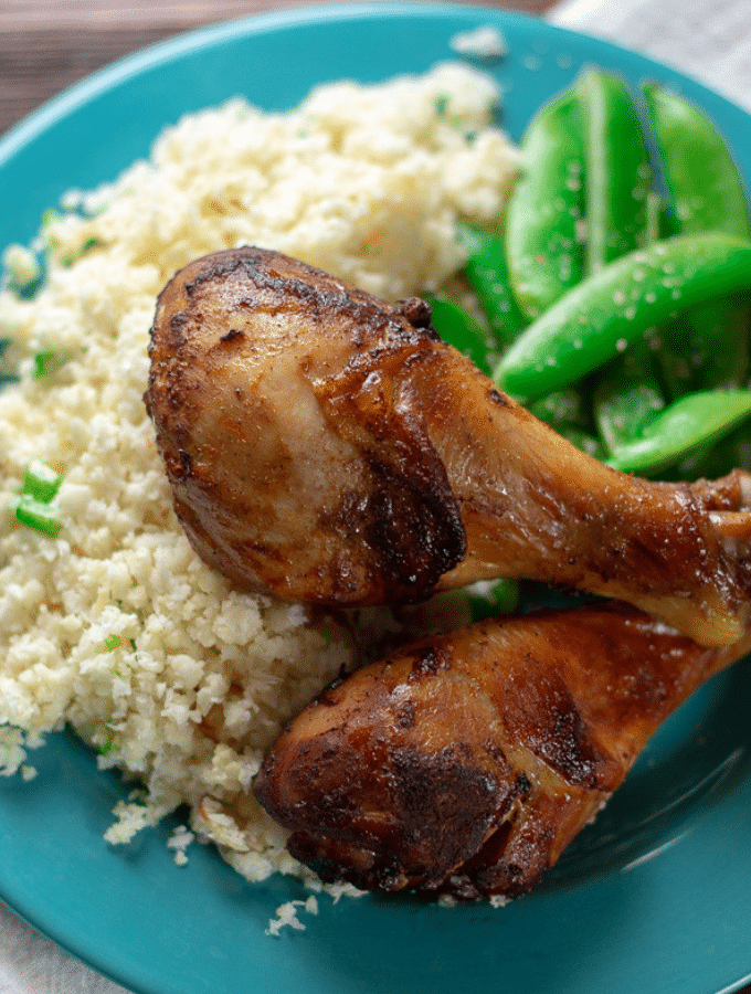 Orange and Five-Spice Roasted Chicken Legs on a blue plate with cauliflower rice and sugar snap peas