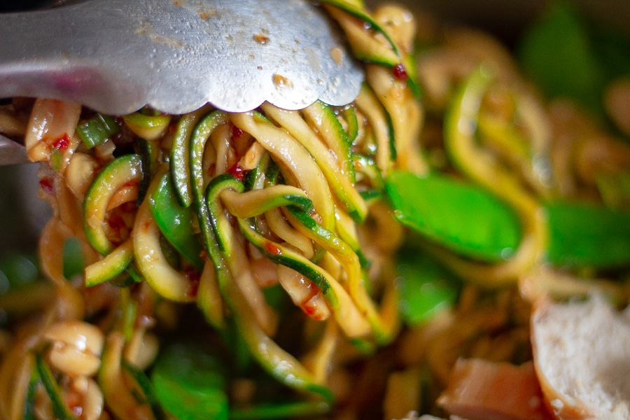 keto kung pao spaghetti being served with metal tongs
