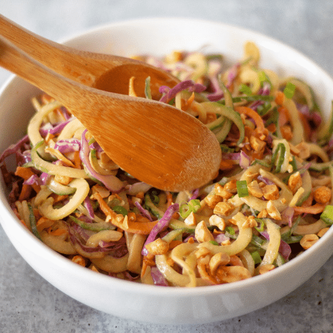 thai peanut sesame cucumber noodles in a large white bowl